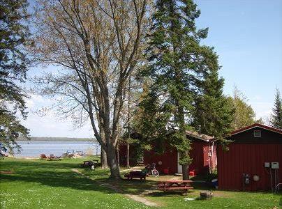 View of cabins, yard and lake.